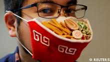 A Japanese designer wears a mask that looks like a ramen bowl
