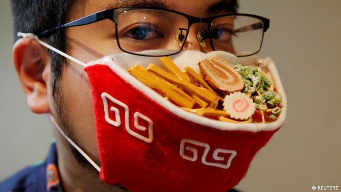 A Japanese designer wears a mask that looks like a ramen bowl