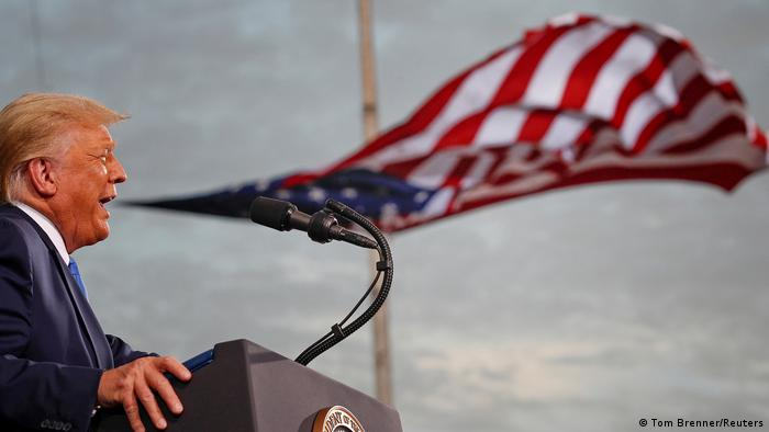 Trump speaking in front of a US flag