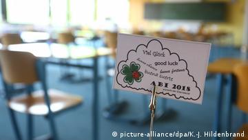Ein Kärtchen mit guten Wünschen für das Abitur 2018 in einem Klassenraum.