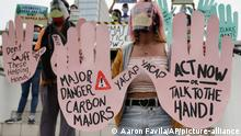 Climate activists in the Philippines hold big cardboard hands saysing act now or talk to the hand