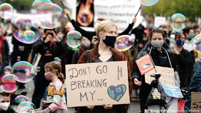 A protester in Berlin holds a sign saying Don't go breaking my heart