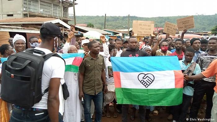 Eine Menschenmenge, sie präsentieren eine Fahne