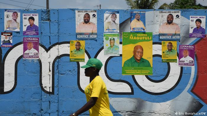 A man walks past a wall with election posters