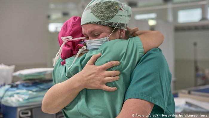 Two nurses wearing face masks hug at a hospital in Barcelona on International Nurses Day.