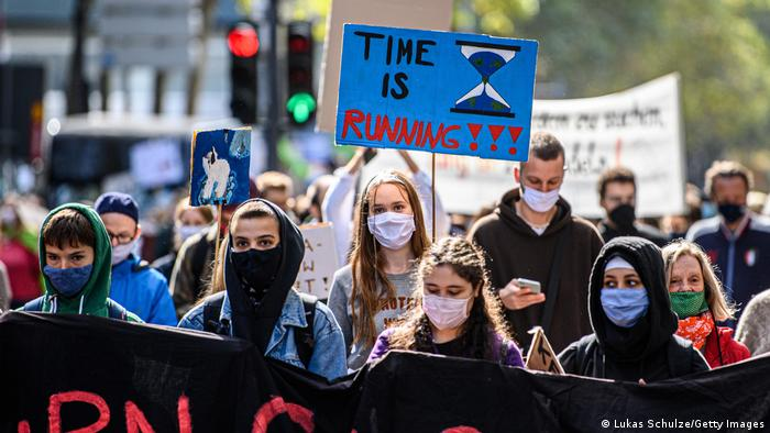 Fridays For Future protesters wearing masks hold a sign that says 'time is running out'