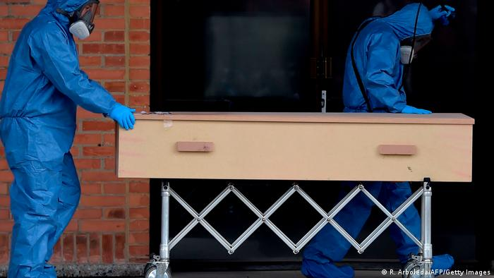 Workers move the coffin of a COVID-19 victim to be cremated at Serafin cemetery in Bogota