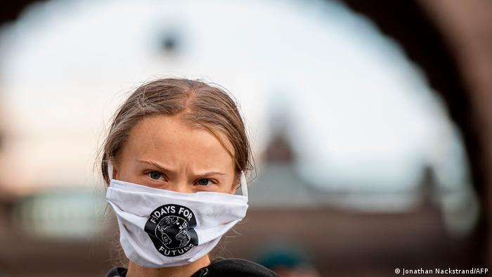 Greta Thunberg, de cabelo preso e usando máscara de proteção com o logo Fridays for Future.