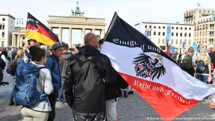 Protester at the Brandenburg Gate in Berlin waving an Imperial Flag