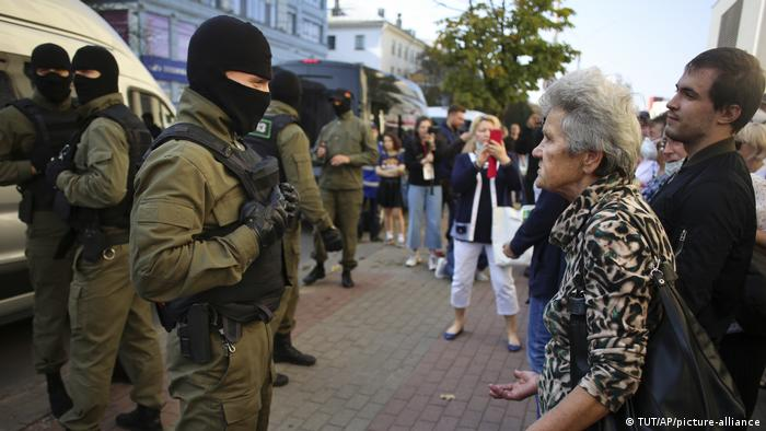 A woman argues with a police officer in Minsk