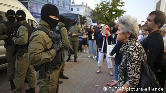 Пожилая женщина стоит перед омоновцем