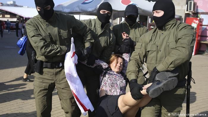 Belarusian security forces carry a woman