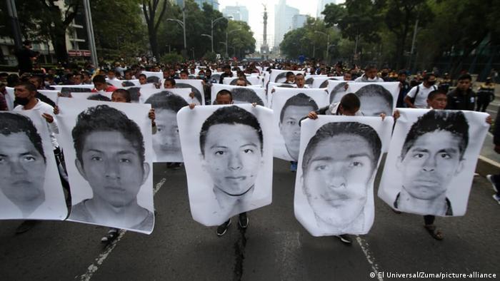 Foto de familiares con fotos de los estudiantes de Ayotzinapa