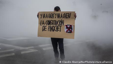 Foto de manifestante en Chile que porta un letrero contra la Constitución de Pinochet en una imagen de archivo