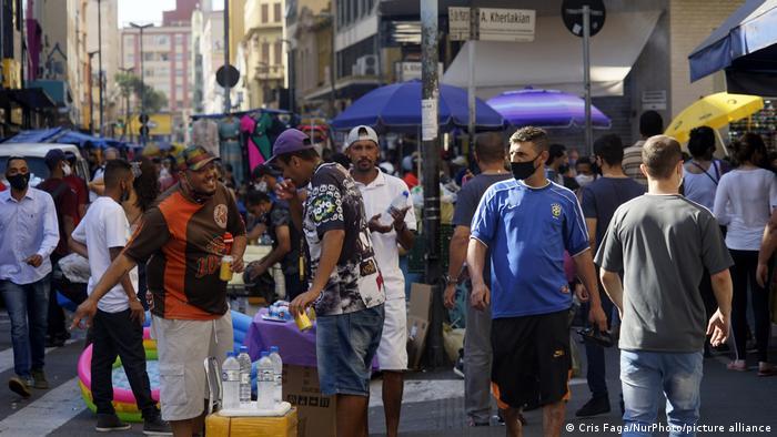 Pessoas em rua movimentada de São Paulo em meio à pandemia