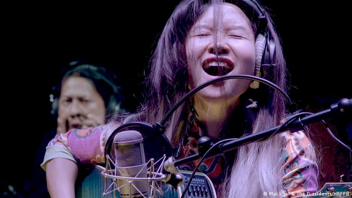 Human Rights Film Festival Berlin: image from the film Mai Khoi & The Dissidents - a young Asian woman with a guitar and a microphone (Mai Khoi & The Dissidents/HRFFB)