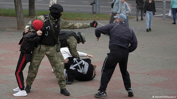 ОМОНовец распыляет в лицо демонстранту слезоточивый газ