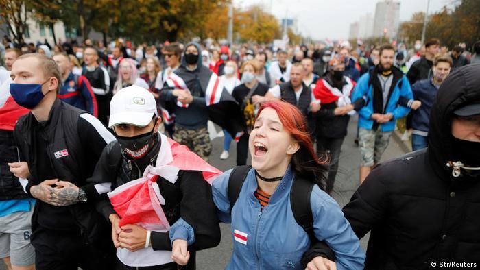 Колонна участников протеста с бело-красно-белыми флагами