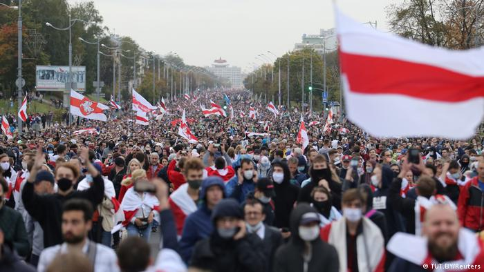 Protesters waving red-and-white opposition flags march in Minsk