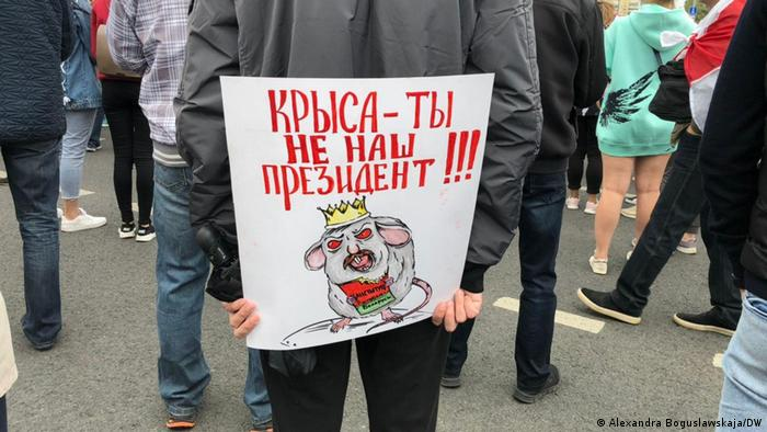 Участник акции протеста с антилукашенковским плакатом
