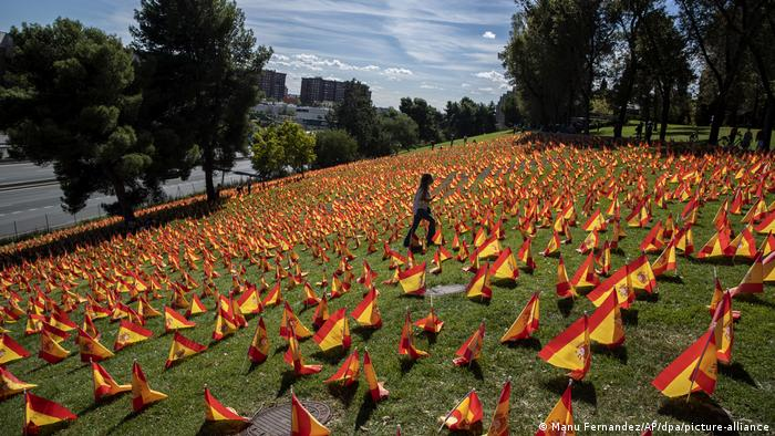 Woman walking across a lawn in the Parque de Roma in Madrid, where 53,000 Spanish flags were planted in the ground in honor of coronavirus victims.