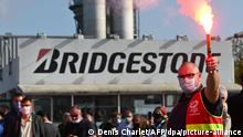 17.09.2020, Frankreich, Béthune: Ein Gewerkschafter zündet während einer Demonstration vor dem Werk des japanischen Reifenherstellers Bridgestone eine Fackel an. Bridgestone hatte zuvor mitgeteilt, das Werk in Béthune komplett schließen zu wollen, denn es gebe Überkapazitäten. Foto: Denis Charlet/AFP/dpa +++ dpa-Bildfunk +++ |