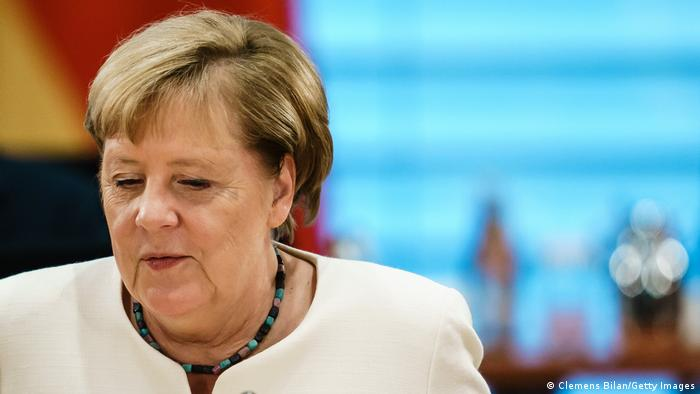 a headshot of Merkel wearing a cream jacket and blue beads around her neck