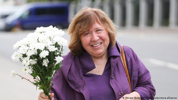Belarusian writer and journalist Svetlana Alexievich holds a bunch of white flowers. She is wearing a purple coat and has a large smile.