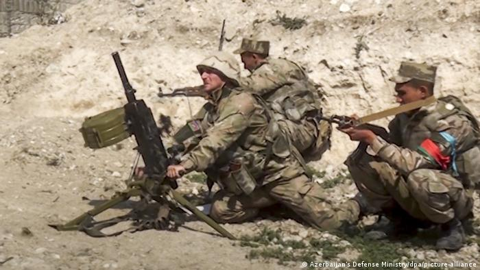 Azerbaijani soldiers fire weapons as the clash with rebels from the disputed Nagorno-Karabakh region
