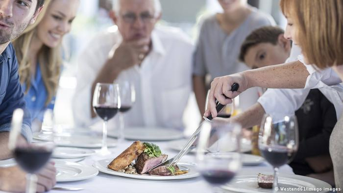 Menschen bei einer Familienfeier beugen sich über einen Braten auf dem Tisch (Westend61/imago images)