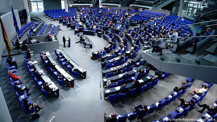 A photograph of the bundestag with lawmakers sitting apart from eachother