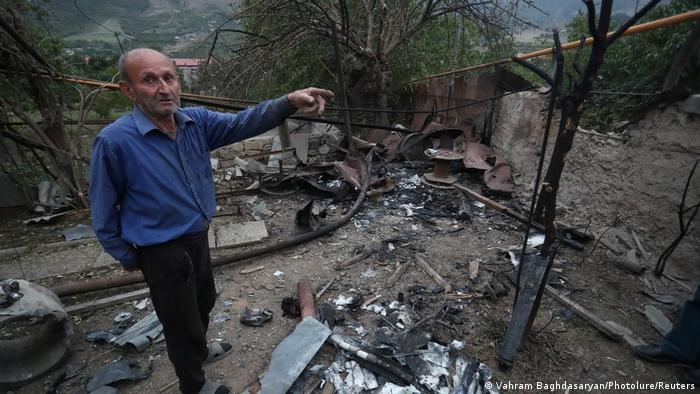 A man stands before a damaged household in Nagorno-Karabakh