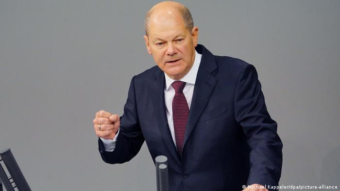 Olaf Scholz wearing a midnight blue suit, white shirt and maroon textured tie. He has his right fist raised and clenched.