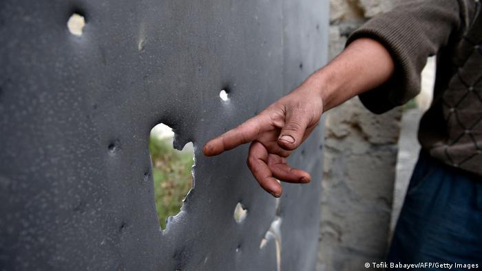 Азербайджанец показывает на дырки от осколков в железном листе