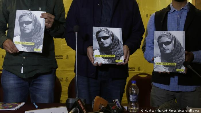 Amnesty International workers hold a copy of a human rights report