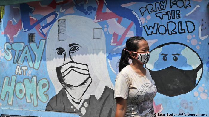 A woman in a facemask walks past a coronavirus-themed mural in Tangerang, Indonesia