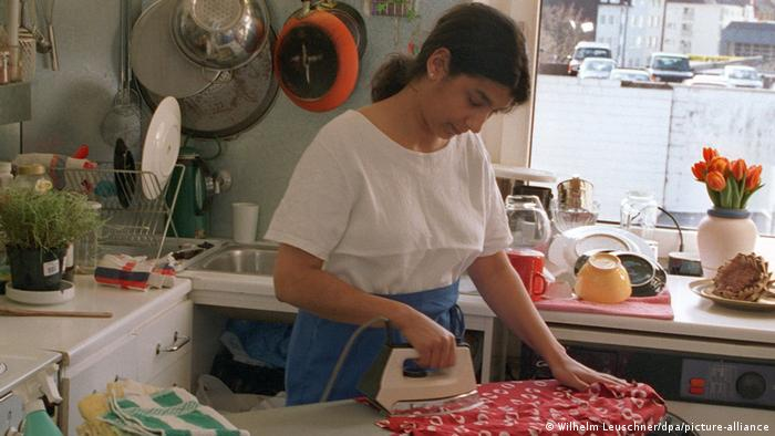 Una mujer planchando en la cocina.