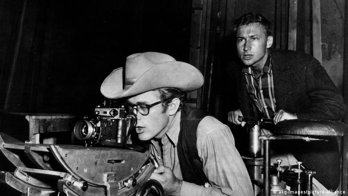 James Dean, mit Hut und Brille, schaut durch eine Kamera  Giganten