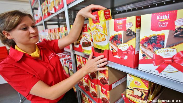 A picture of Kathi employee Bianca Skudlik sorting baking mixes in a shelve at the company's headquarters in Halle, eastern Germany.