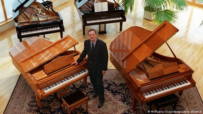 Christian Blüthner-Haessler from the pianomaker Blüthner pictured standing between two pianos.