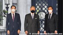 Three members of Belgium's new coalition posse for a photograph in suits, wearing face masks