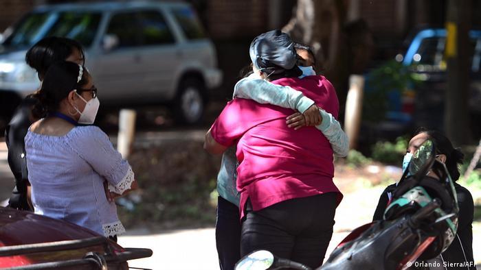 Parientes y amigos de Luis Almendares se abrazan mientras esperan los restos del periodista Luis Almendares.
