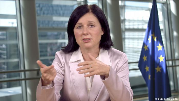 Vizepräsidentin der EU-Kommission Vera Jourova sitzt an einem Tisch, im Hintergrund ist eine EU-Flagge zu sehen