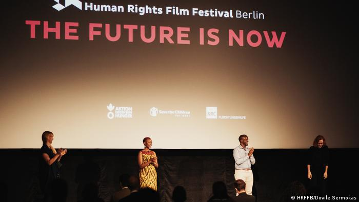 Four people on a stage in front of a screen showing the logo 'The Future is Now' Human Rights Film Festival Berlin (HRFFB/Dovile Sermokas)