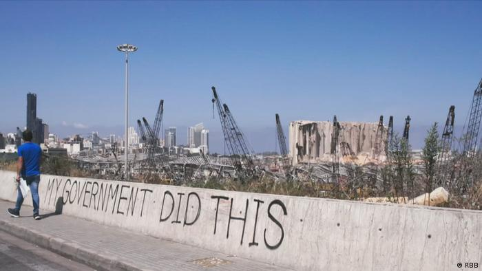 Graffiti saying 'My government did this' against a backdrop of the ruined port