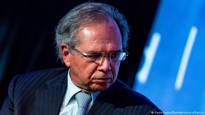 Paulo Guedes, de óculos, olha para o lado. Ele veste terno escuro risca de giz e gravata azul estampada.