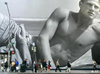 Pedestrians walk pass a giant display ad for the retailer, Abercrombie & Fitch