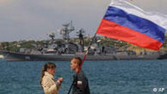 A man holding a Russian flag speaks with a girl