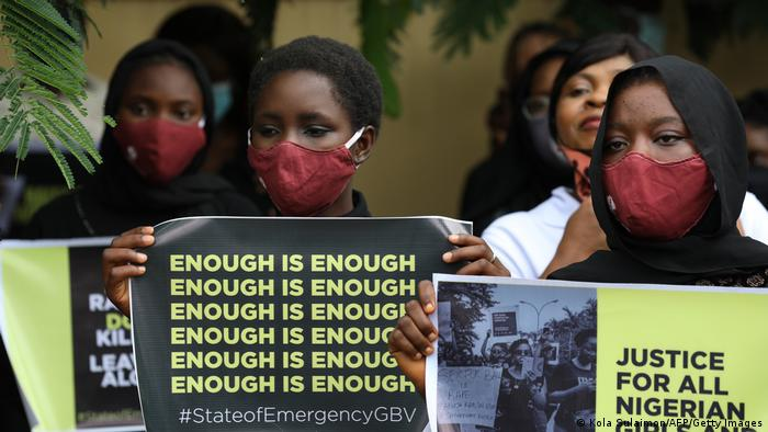 Nigerian women in red face masks hold up posters decrying gender-based violence