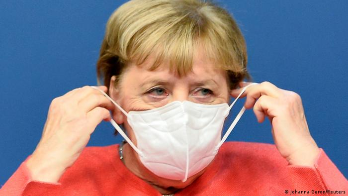 Ангела Меркель одевает защитную маску